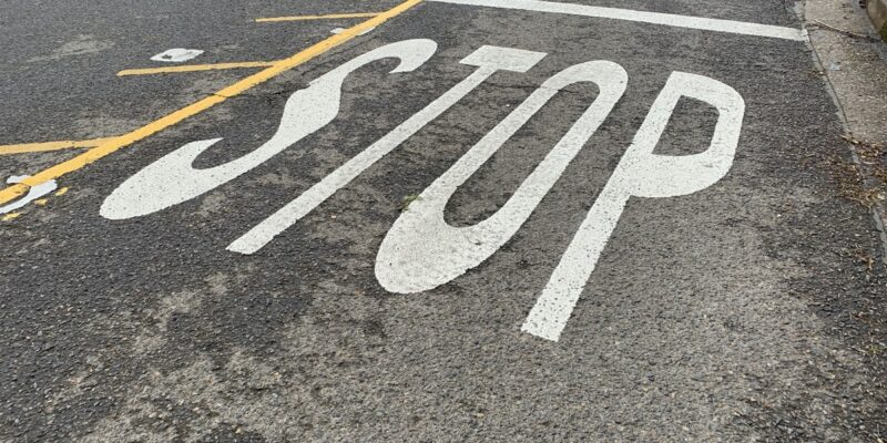 Photo of the word Stop painted on a street